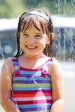 Summer Fun. A big smile on a little dark haired 4 year old girl playing in the sprinkler. Shallow depth of field Royalty Free Stock Image