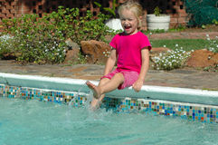 Summer fun. A beautiful caucasian girl child in pink clothes splashing the water in the swimmingpool with her white feet having much fun in summer Stock Images