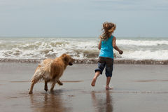 Summer fun. Little girl and her dog running into the ocean Royalty Free Stock Image