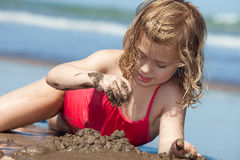 Summer fun. Little girl playing with sand on the beach Stock Photos