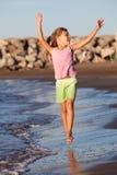 Summer fun. Little girl running by the ocean Stock Images