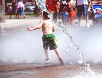 Summer Fun. Boy playing in a fountain Royalty Free Stock Image