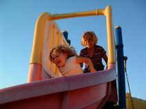 Summer Fun. Two girls playing on slides at twilight Royalty Free Stock Photo