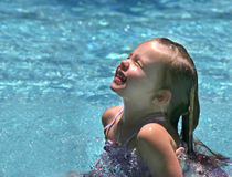 Summer Fun. Young girl playing in sparkling blue pool Royalty Free Stock Photos
