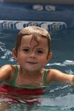 Summer fun. Young girl smiling in pool water royalty free stock images