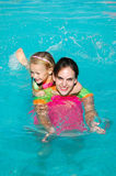 Summer fun. A beautiful brunette young teenager and a pretty blond caucasian white girl child with happy smiling expression in their faces having great fun while Royalty Free Stock Photography