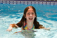 Summer fun. Young girl happy to be swimming in the pool Royalty Free Stock Photos