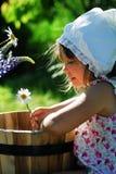 Summer fun. A cute little girl looking on her flower Stock Photos