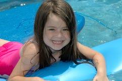 Summer Fun. Little girl playing in backyard pool Stock Image
