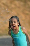 Summer Fun. A young girl plays in a water fountain Stock Photo
