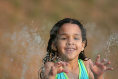 Summer Fun. A young girl plays in a water fountain Stock Image