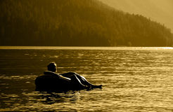 Summer Fun. A young woman relaxing in a lake Stock Images