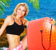 Summer fun on the beach. Beautiful sporty female holding body board, outdoor beach portrait, water sport, healthy lifestyle concept Stock Photos