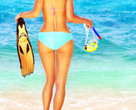 Summer fun on the beach. Beautiful female on the beach holding snorkeling equipment, water sport, healthy lifestyle concept Stock Image