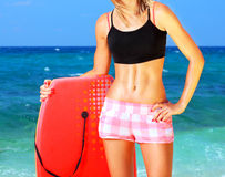 Summer fun on the beach. Beautiful sporty female holding body board, outdoor fun on the beach , water sport, healthy lifestyle concept Royalty Free Stock Photo