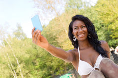 Summer fun at the beach. Young woman at the beach taking a selfie Royalty Free Stock Photos