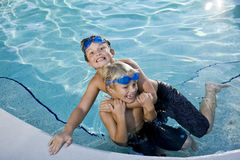 Summer fun, boys playing in swimming pool. Boys will be boys - playing on side of swimming pool, 7 and 9 years Stock Photography