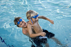 Summer fun, boys playing in swimming pool. Boys will be boys - playing on side of swimming pool, 7 and 9 years Royalty Free Stock Images