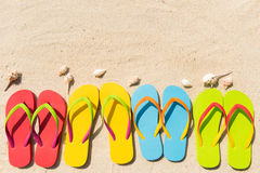 Summer fun. Four pairs of flip flops in a row on beach Stock Photo
