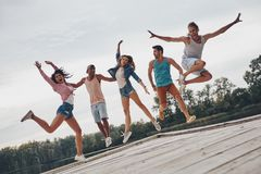 Summer fun. Full length of young people in casual wear smiling and gesturing while jumping on the pier stock photos