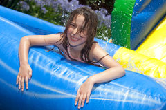 Summer fun. Happy girl in inflatable pool royalty free stock image
