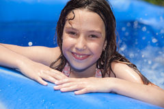 Summer fun. Happy girl in inflatable pool royalty free stock photography