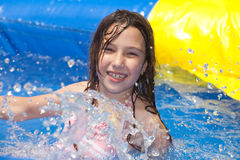 Summer fun. Happy girl in inflatable pool stock photos