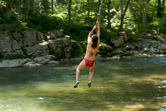 Summer fun II. Girl on rope swing over river royalty free stock images