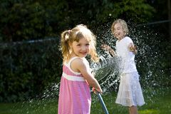 Summer Fun for Kids. Two young girls having a water fight Royalty Free Stock Photos