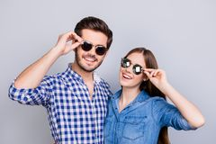 Summer and fun mood. Young students are wearing trendy sunglasses and smile, in casual shirts, posing on the pure background. Pret. Ty couple Royalty Free Stock Image