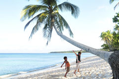 Summer Fun, children play. Picture of two boys frolicking in the sun and sand under the coconut tree in the Philippines Asia Royalty Free Stock Images