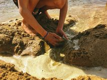 Girl playing with her hands in the sand and water at the beach stock image