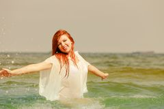 Redhead woman playing in water during summertime royalty free stock images