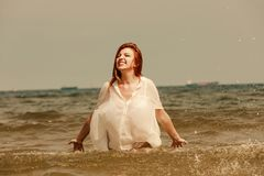 Redhead woman playing in water during summertime stock photography