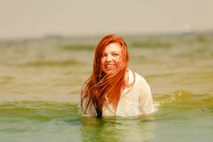 Redhead woman playing in water during summertime stock image