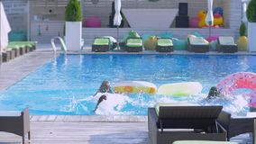 Summer fun at resort, company young women in bathing suits with long hair and beautiful bodies run with rubber circles