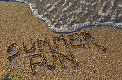 Summer fun by the seashore. Summer fun text written on the sand and foamy wave Royalty Free Stock Photography