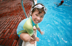 Summer fun splash pool. Smiling girl touch blue water in the pool Royalty Free Stock Photo