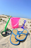 Summer Fun in the Sun. Summertime fun at the beach.  For a child they bring their pale and shovel, snorkel with mask and a pair of flipflop slippers to walk in Stock Images