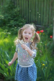 Summer fun, sweet little girl blowing dandelion in the backyard Royalty Free Stock Photo