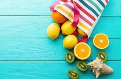 Free Summer Fun Time And Fruits On Blue Wooden Background. Mock Up And Picturesque. Orange, Lemon, Kiwi Fruit In Bag And Shell Royalty Free Stock Photos - 114045148