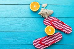 Summer fun time and flip flops. Sea shell. Slippers and orange fruit on blue wooden background. Mock up and picturesque. Top view. Summer fun time and flip royalty free stock photos
