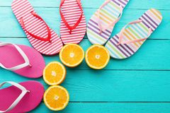 Summer fun time and flip flops. Slippers and orange fruit on blue wooden background. Mock up and picturesque. Top view. Copy space.  Royalty Free Stock Photos