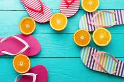 Summer fun time and flip flops. Slippers and orange fruit on blue wooden background. Mock up and picturesque. Top view. Copy space.  royalty free stock photography