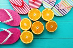 Summer fun time and flip flops. Slippers and orange fruit on blue wooden background. Mock up and picturesque. Top view. Copy space.  royalty free stock photo