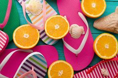 Summer fun time and flip flops. Slippers and orange fruit on blue wooden background. Mock up and picturesque. Top view. Sandals.  royalty free stock photos