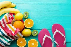 Summer fun time. Fruits on blue wooden background. Orange, lemon, kiwi, banana fruit in bag and flip flops on the floor. Top view. Summer fun time and fruits on stock photo
