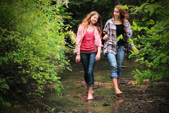 Summer Fun. Two pretty young country girls walking through a creek bed in Summer with bare feet exploring the woods, both with long hair and smiling. Shallow Stock Photo