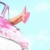 Summer fun vintage car. Legs showing from pink vintage retro car. Freedom, travel and vacation road trip concept lifestyle image with woman and copy space on Stock Photos