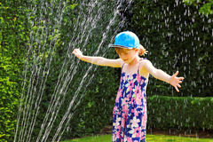Summer fun with water sprinkler Stock Photo